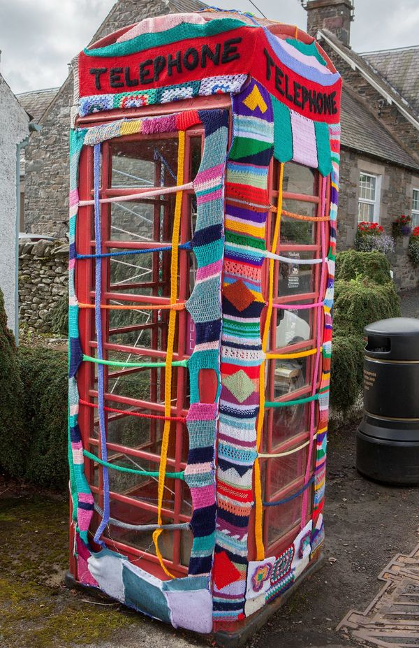 "Women from Scotland have formed a team of ""guerrilla knitters."" They have decorated this phone booth with crochet and knitted"