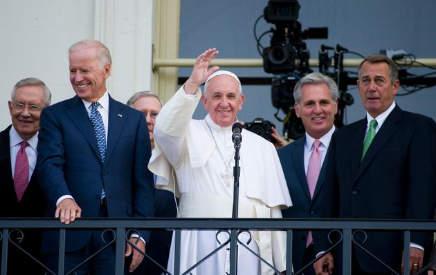 Pope Francis, joined by politicians, waves from the Capitol building following his speech to a joint...
