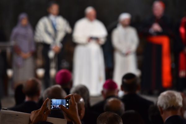 An attendee takes photos with a cell phone as Pope Francis attends a multi-religious service for the victims of 9/11 at the m