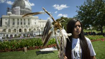 An activist protests on Capitol Hill July 22, 2015 in Washington, DC. Members of the San Carlos Apache Nation and other activists gathered to protest the a section of the National Defense Authorization Act that would turn over parts of Oak Flat that are sacred to the Apache to a foreign copper mining company. AFP PHOTO/BRENDAN SMIALOWSKI        (Photo credit should read BRENDAN SMIALOWSKI/AFP/Getty Images)