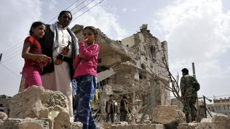 SANAA, YEMEN - JULY 3: A man with two child girls stand among the rubble of the destroyed buildings after Saudi-led coalition air strikes hit the residential areas in Hashish region of Sanaa, Yemeni capital on July 03, 2015. (Photo by Mohammed Hamoud/Anadolu Agency/Getty Images)