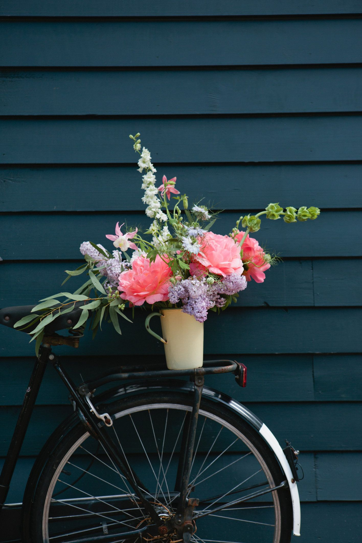 A beautiful arrangement of flowers on the back of a vintage black Dutch bicycle.