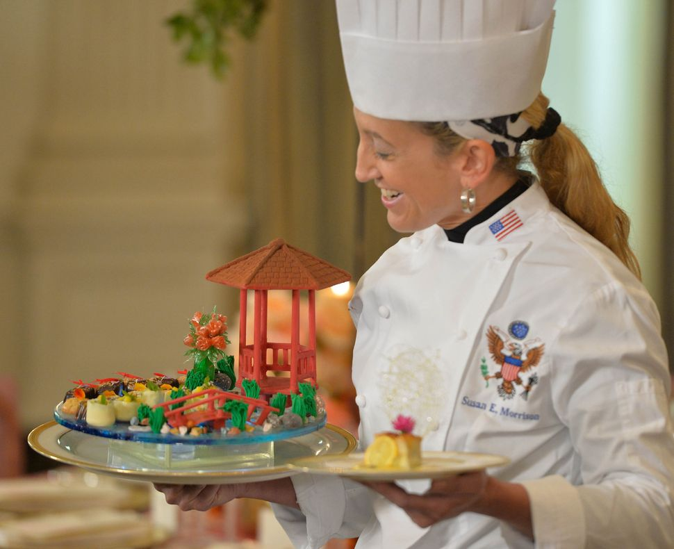 The pastry chef displays a dessert featuring a Chinese-style chocolate pavilion and bridge.