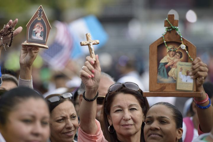People hold up religious items while waiting for Pope Francis at Independence Hall on September 26, 2015 in Philadelphia, Pen