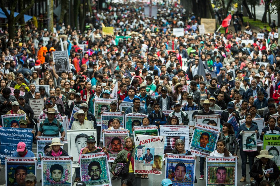 Relatives of the 43 missing students of Ayotzinapa march during the one-year anniversary of their disappearance in Mexico&nbs