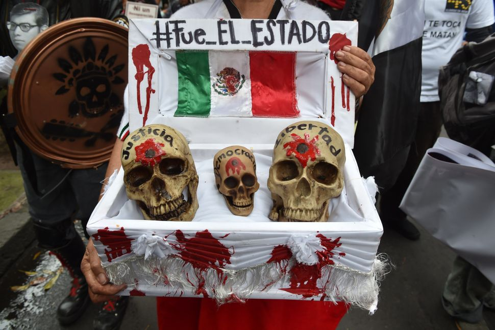 """A woman holds a fake coffin with skulls markedjustice, democracy and freedom, below a banner reading """"It was the state"""""""