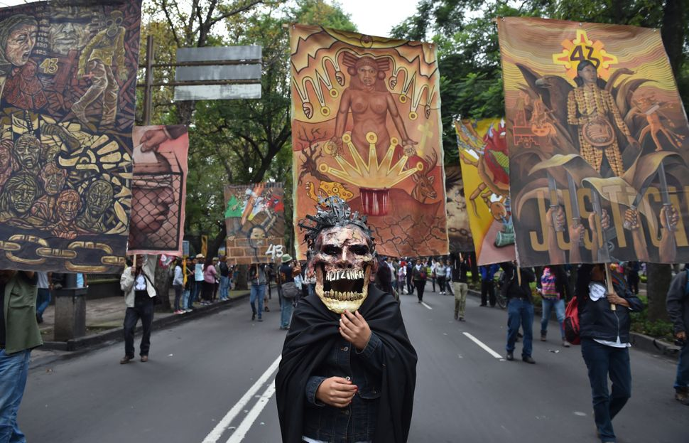 Thousands commemorate the first anniversary of the students' disappearance by marching in Mexico City.
