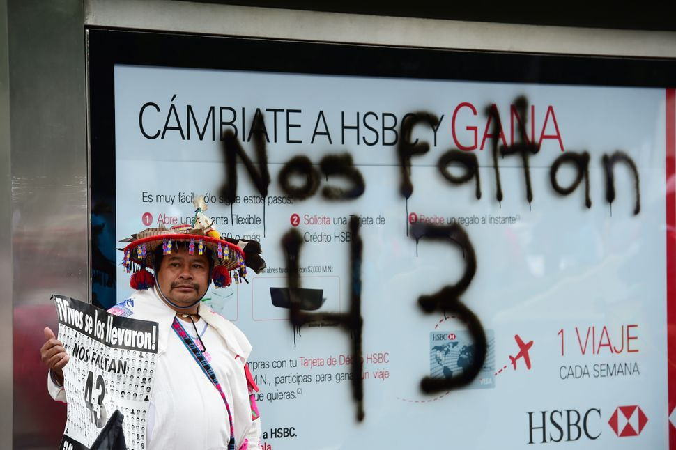 """Some protesters held signs reading """"Nos faltan 43,"""" Spanish for 'We are missing 43."""""""