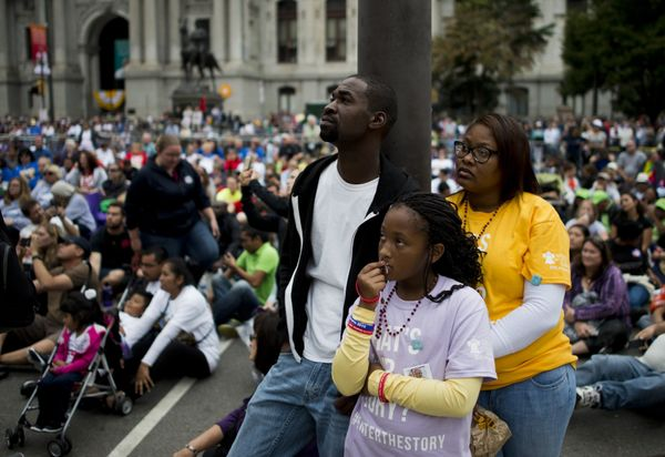 A family watches a Mass on a large screen with Pope Francis in downtown Philadelphia.