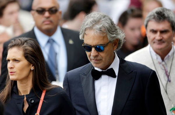 Italian tenor Andrea Bocelli (C) walks to receive communion.