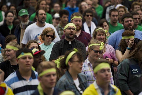 Catholic devotees sing as they watch Pope Francis' Mass.