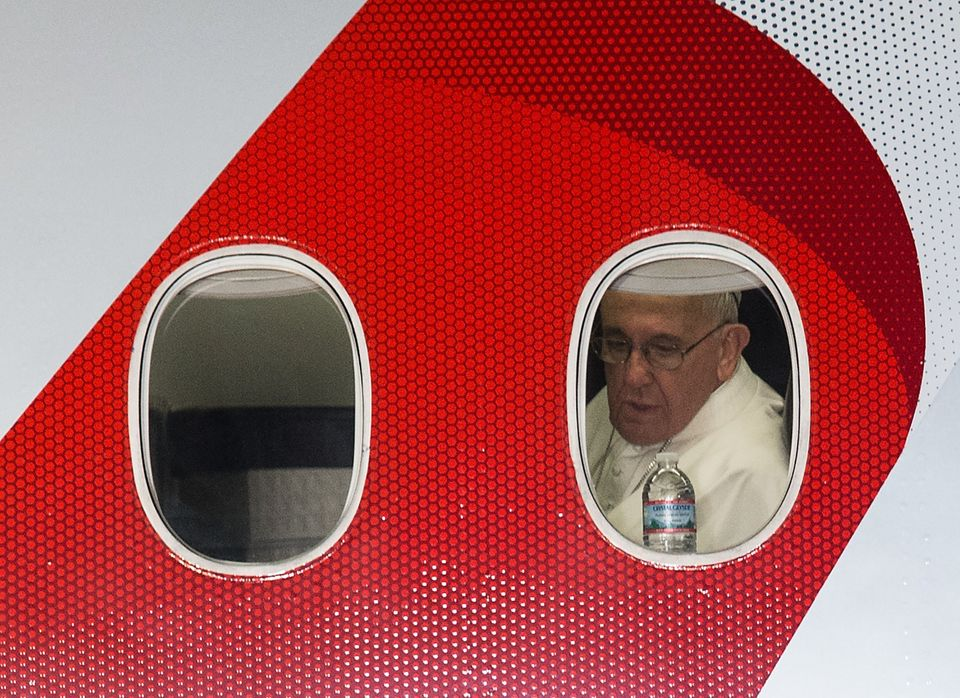 Pope Francis looks out the window of his plane before departing Philadelphia on September 27, 2015 at the end of his six-day