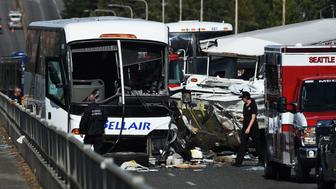 A medical examiner checks the scene of a crash between a tour bus and a tourist duck boat on the Aurora Bridge in Seattle, Washington on September 24, 2015. At least four people were killed and several were critically injured when a bus collided with a tour vehicle on a bridge in the US West Coast city of Seattle, officials said. AFP PHOTO/ MARK RALSTON        (Photo credit should read MARK RALSTON/AFP/Getty Images)