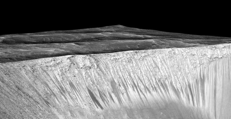 Dark narrow streaks called recurring slope lineae are shown emanating out of the walls of Garni crater on Mars. The stre
