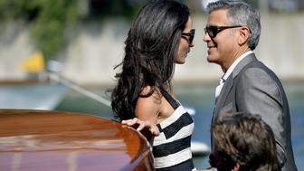 US actor George Clooney (R) and his Lebanon-born British fiancee Amal Alamuddin take a taxiboat upon their arrival in Venice on September 26, 2014, on the eve of their wedding. The party of the year is happening here: the fresco-adorned Aman hotel on Venice's Grand Canal is feverishly preparing for George Clooney's wedding to Amal Alamuddin, his Lebanon-born British fiancee. Hollywood stars and the world's paparazzi have already begun arriving for the nuptials of the world's most sought-after catch, who will, sources said, celebrate with 136 guests at the exclusive seven-star hotel in the 450-year-old Palazzo Papadopoli. AFP PHOTO / ANDREAS SOLARO        (Photo credit should read ANDREAS SOLARO/AFP/Getty Images)