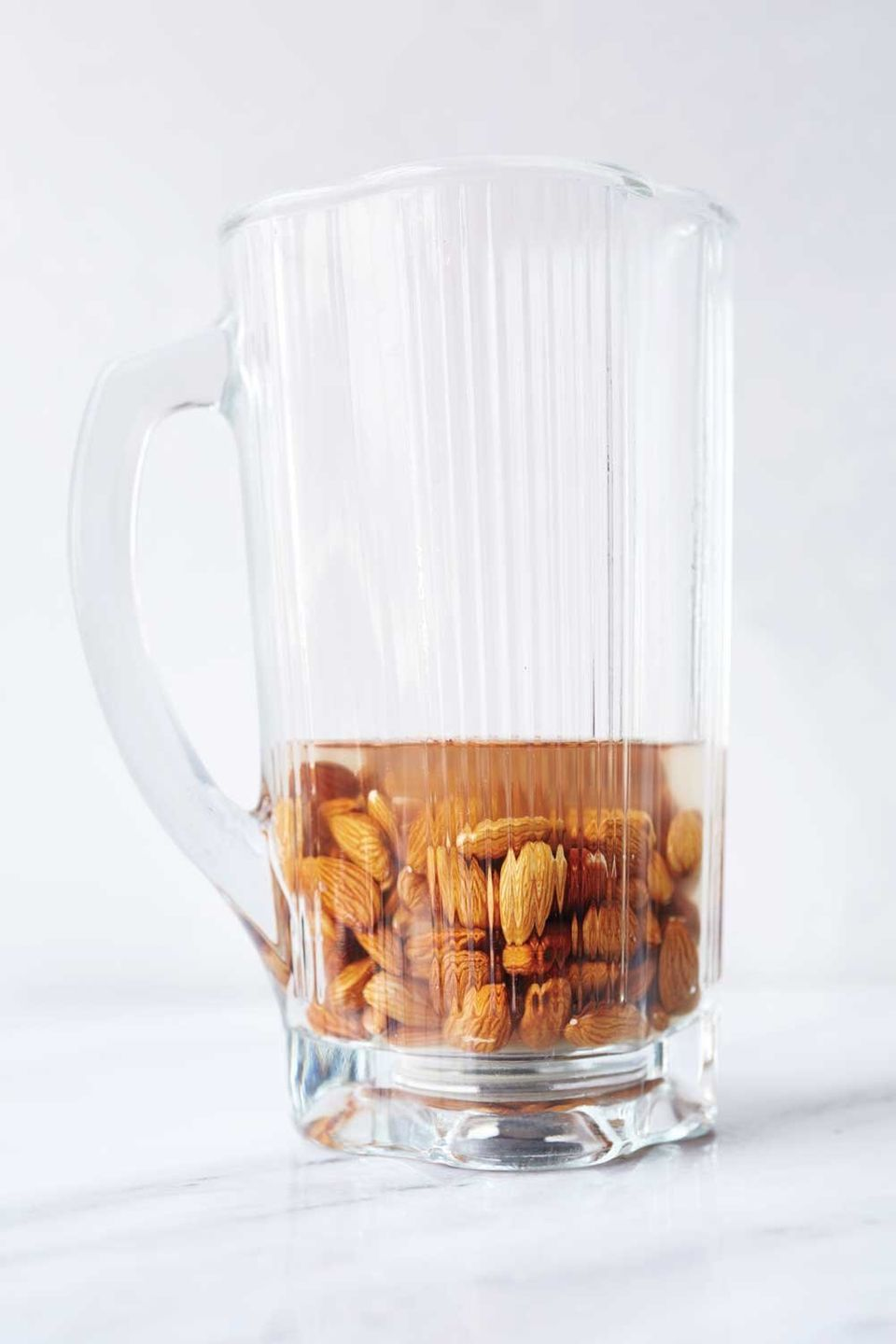 Place 1 cup whole raw nuts (almonds are shown, but you can also use cashews, pistachios, or hazelnuts) with an equal amount o