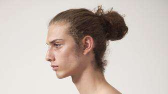 Young male model with long hair bare chest studio