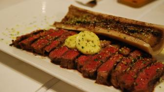 Grilled Ribeye with bone marrow and anchovy butter as served in leading Italian restaurant in Hong Kong.