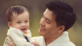A smiling young father holds his happy baby boy with obvious love and pride. The photo was taken outdoors in natural light.