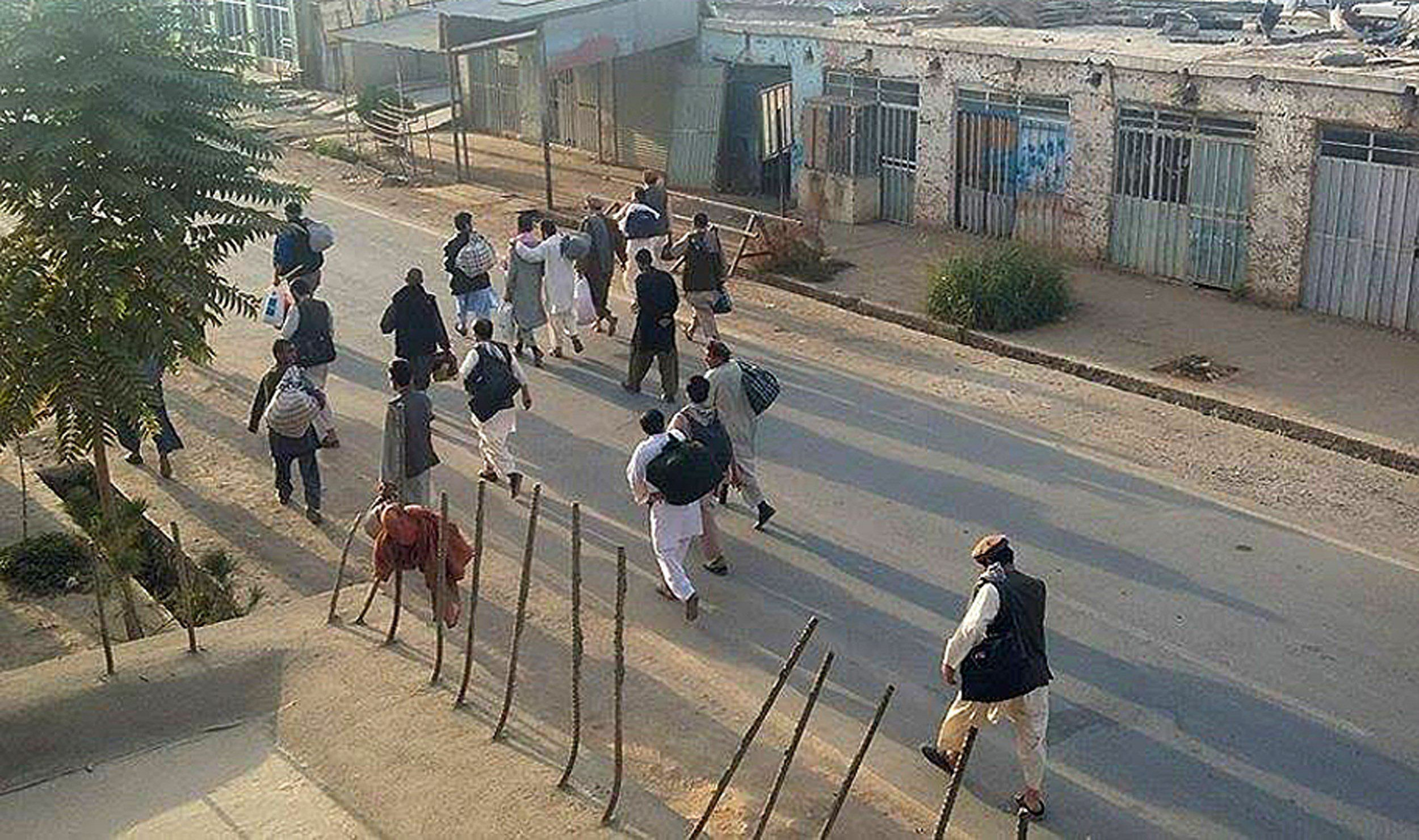 In this photograph taken on September 28, 2015, prisoners walk down a street after Taliban insurgents released them from the main jail in Kunduz. Afghanistan on September 29, 2015, mobilised reinforcements for a counter-offensive to take back Kunduz, a day after Taliban insurgents overran the strategic northern city in their biggest victory since being ousted from power in 2001.   AFP PHOTO        (Photo credit should read STR/AFP/Getty Images)
