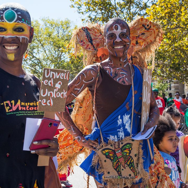 Parade participants march with a tribal themed group wearing colorful face paint. The 46th Annual African-American Day Parade