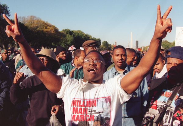 A man raises his hands in the air as he celebrates during Million Man March on the Mall, 16 October 1995, in Washington DC. T