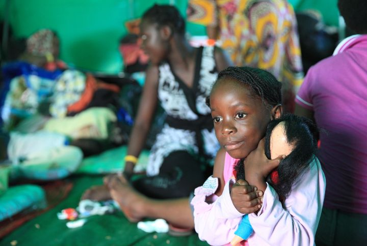 Five-year-old Nema Shukuru from Congo hugs her doll in a refugee camp set up on a sports field in Isipingo Township on April