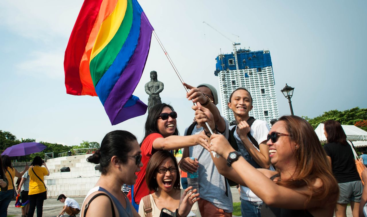 People wave a flag during a Pride march on June 17, 2015, in Manila, which has a vibrant LGBT movement.