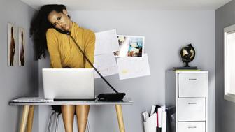 business woman in small office, by her computer, on the phone, looking stressed - her head touching the ceiling