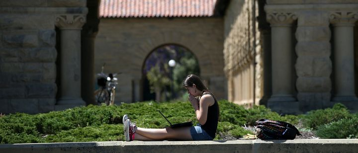 A woman studies on the campus of Stanford University.