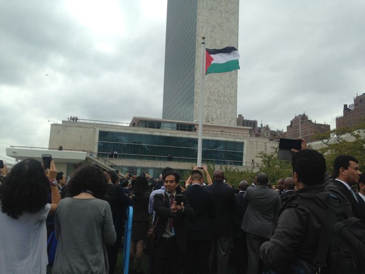 A man takes a selfie in front of the Palestinian flag after it was raised at the U.N. headquarters for the first time on Sept