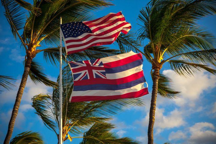A U.S. flag and a Hawaii state flag fly together.