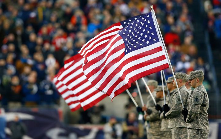 Military members hold flags before a playoffgame between the New England Patriots and the Baltimore Ravens at Gillette