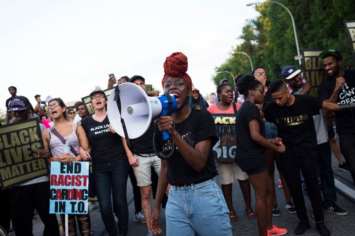 Tari Ngangura screams into a microphone during a Black Lives Matter protest