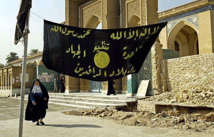 An Iraqi woman walks past a jihadi banner in Baghdad in 2004.