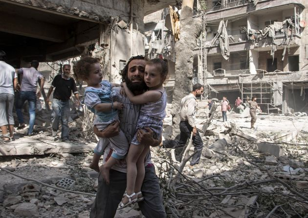 A Syrian man carries his two girls as he walks across the rubble following an airstrike in Aleppo on...