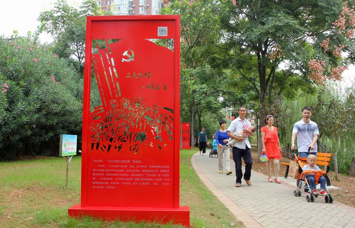 "People walk past a statue of the Communist Party's ""Three Rules of Discipline and Eight Points for Attention."""