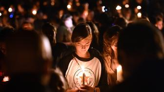 A girl prays during a vigil in Roseburg, Oregon on October 1, 2015, for ten people killed and seven others wounded in a shooting at a community college in the western US state of Oregon. The 26-year-old gunman, identified by US media as Chris Harper Mercer, was killed following a shootout with police. A visibly angry President Barack Obama made an impassioned plea for gun control in the wake of the shooting, blasting Congress for its failure to act in the face of 'routine' mass killings.  AFP PHOTO/JOSH EDELSON        (Photo credit should read Josh Edelson/AFP/Getty Images)
