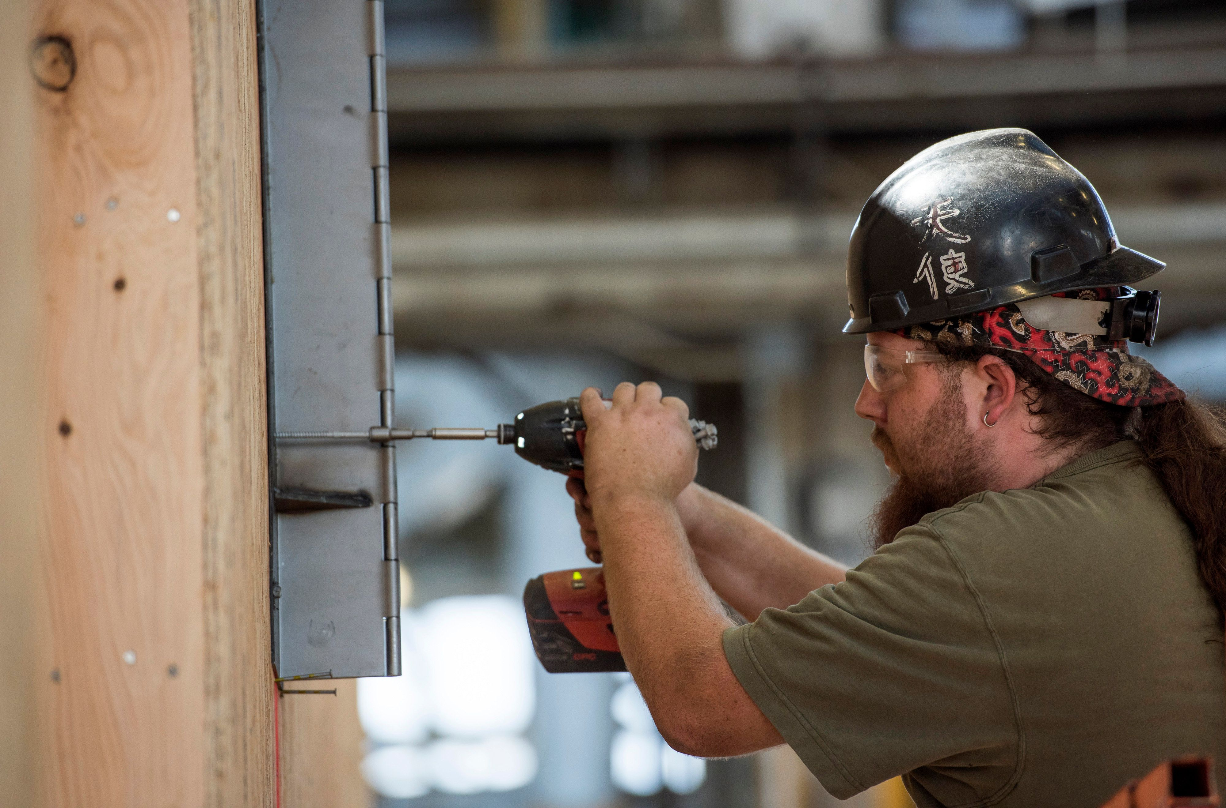 A worker attaches a metal box to a house being constructed at the BLU Homes Inc. production facility in Vallejo, California, U.S., on Friday, Sept. 11, 2015. BLU Homes operates as an environmentally friendly house building firm providing residential, commercial and institutional buyers economical houses with a green theme by it's use of steel and wood, as well as a folding technology for the purpose of reducing carbon footprints. Photographer: David Paul Morris/Bloomberg via Getty Images