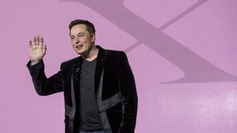 Elon Musk, chairman and chief executive officer of Tesla Motors Inc., gestures as he unveils the Model X sport utility vehicle (SUV) during an event in Fremont, California, U.S., on Tuesday, Sept. 29, 2015. Musk handed over the first six Model X SUVs to owners in California Tuesday night, as Tesla reached a milestone of having two all-electric vehicles in production at the same time. Photographer: David Paul Morris/Bloomberg via Getty Images