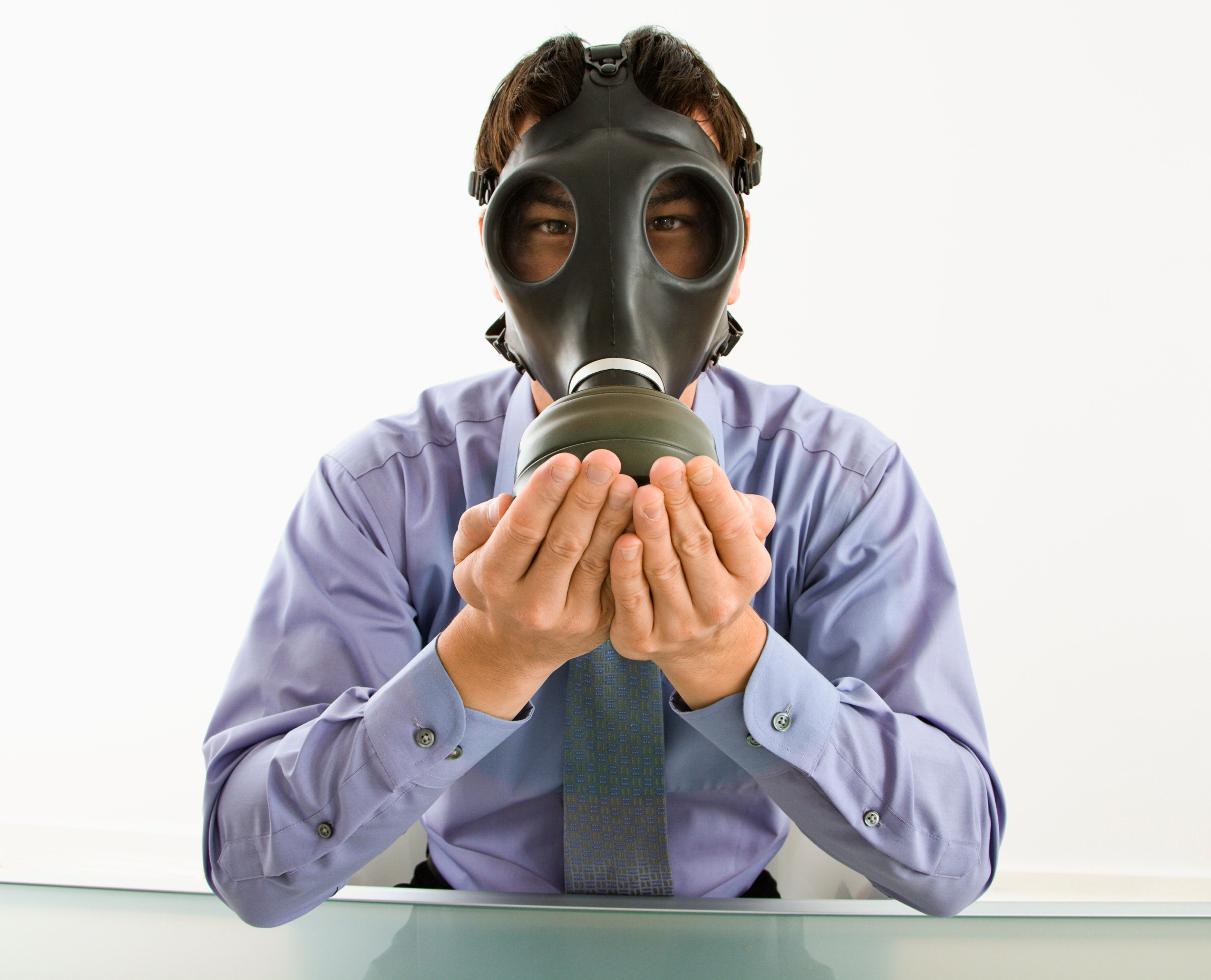 Man wearing gas mask with hands over mouth.