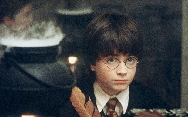 """RADCLIFF...TO GO WITH STORY TITLED POTTER COUNTDOWN--FILE--Actor Daniel Radcliffe writes with a quill in a scene from Warner Bros. """"Harry Potter and the Philosopher's Stone,"""" in this undated promotional photo. The film has its world premiere in London this weekend and hits theaters Nov. 16. Based on the first of author J.K. Rowling's best-selling series, the movie follows the adventures of Harry, an orphan boy who is invited to become a student at the Hogwart's School of Witchcraft and Wizardry. The movie faces huge expectations not only among fans, but at the box office, too. (AP Photo/Warners Bros. Pictures, Peter Mountain/FILE)"""