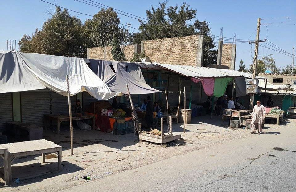 Afghan vendors wait at a row of roadside shops in Kunduz on October 4, 2015, as Afghan forces, backed up by their NATO allies