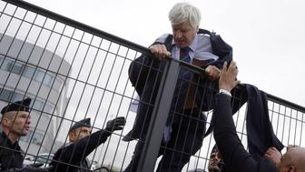 Director of Air France in Orly Pierre Plissonnier, nearly shirtless, tries to cross a fence, helped by security and police officers, after several hundred of employees invaded the offices of Air France, interrupting the meeting of the Central Committee (CCE) in Roissy-en-France, on October 5, 2015. Air France-KLM unveiled a revamped restructuring plan on October 5 that could lead to 2,900 job losses after pilots for the struggling airline refused to accept a proposal to work longer hours. AFP PHOTO / KENZO TRIBOUILLARD        (Photo credit should read KENZO TRIBOUILLARD/AFP/Getty Images)