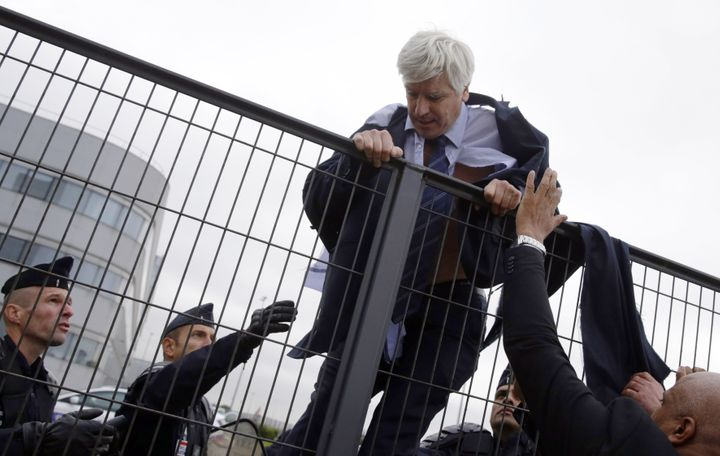 Director of Air France in Orly Pierre Plissonnier, nearly shirtless, tries to cross a fence, helped by security and police of