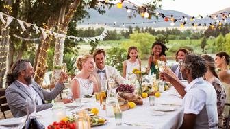 Young couple and their guests sitting at table during wedding reception in garden