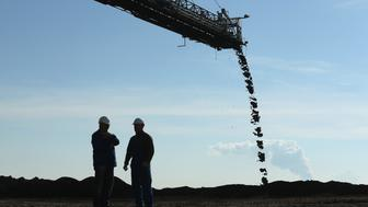 WELZOW, GERMANY - SEPTEMBER 25:  Workers stand under a a mobile machine called a spreader depositing soil removed from one end of the Welzow Sued open-pit lignite coal mine to allow excavators to reach the coal underneath on September 25, 2015 near Welzow, Germany. The Welzow Sued mine feeds the Schwarze Pumpe and Jaenschwalde power stations and is owned by Vattenfall, the Swedish energy company that recently announced it will sell its eastern German coal mines and power plants. Before the communist government of East Germany collapsed in 1989 open-pit coal mines were a vital source of employment in the region and their decline has pulled the local economy down with them. 25 years since German reunification eastern Germany is struggling with a low birth rate, rural emigration and unemployment rates higher than in western Germany. The Welzow Sued mine is one of five left in the Lausatz region from 17 that existed in 1989. It is scheduled to remain in operation until 2042.  (Photo by Sean Gallup/Getty Images)
