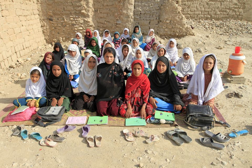 Jalalabad, Afghanistan --- Teacher Mahajera Armani and her class of girls pose for a picture at their study open area.