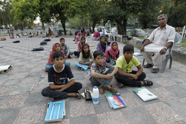 Islamabad, Pakistan -Master Mohammad Ayoub poses with his fifth grade students at a local park.Ayoub, a Pakistani