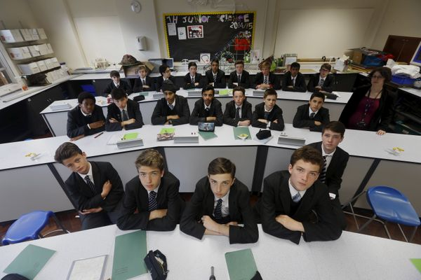 London, England --- Year Nine Biology boys class pose for a picture with teacher Suzanne Veitch in their classroom at Forest